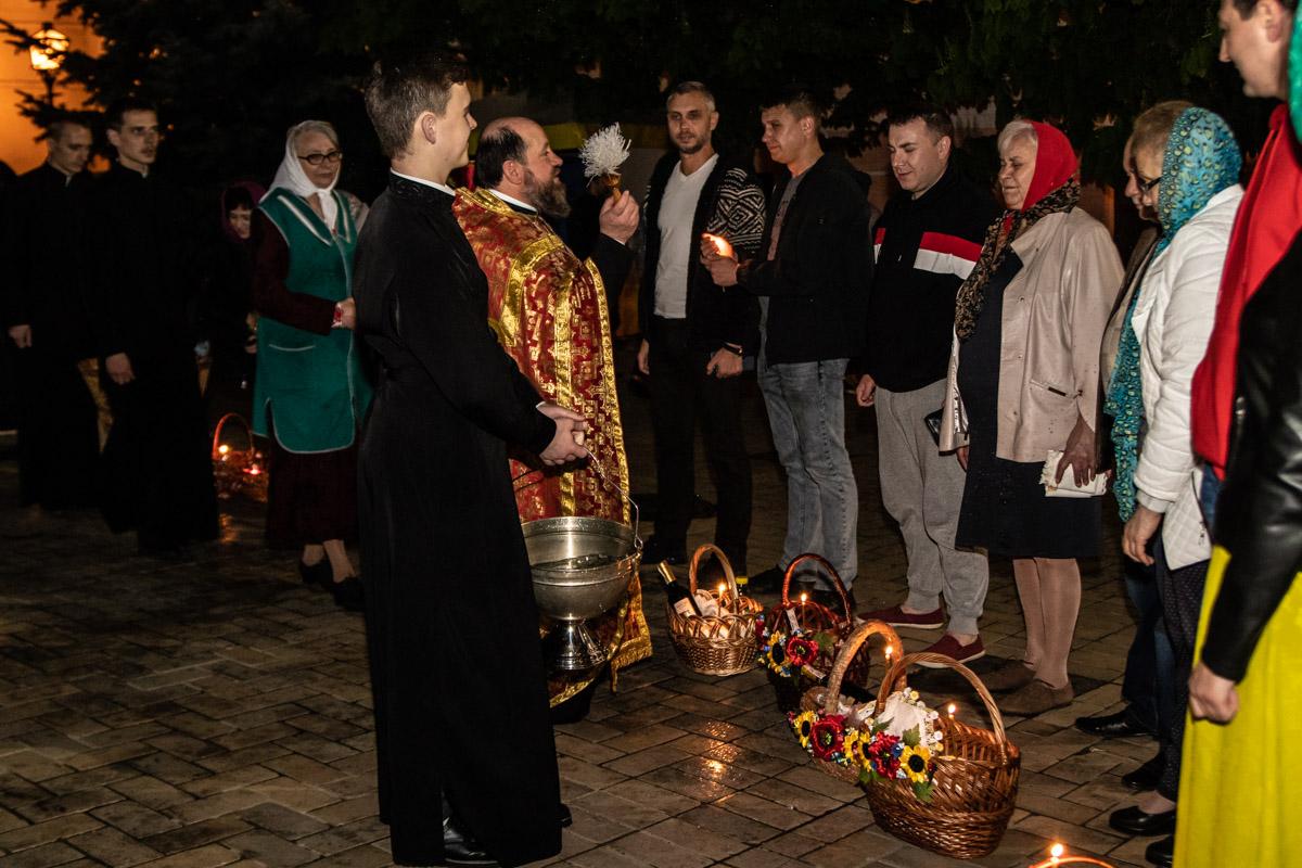 Священнослужитель освящает пасхальные корзины прихожан