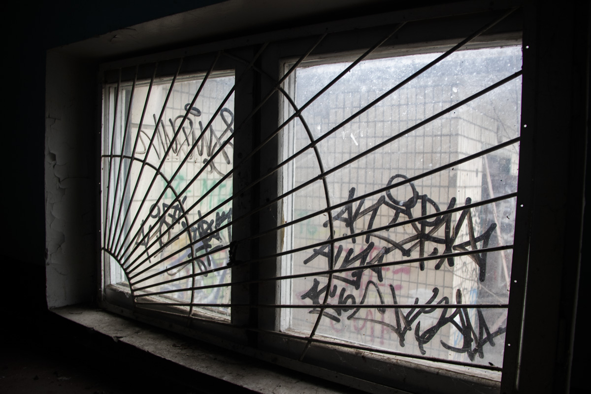 Окна и стены здания исписали уличными граффити