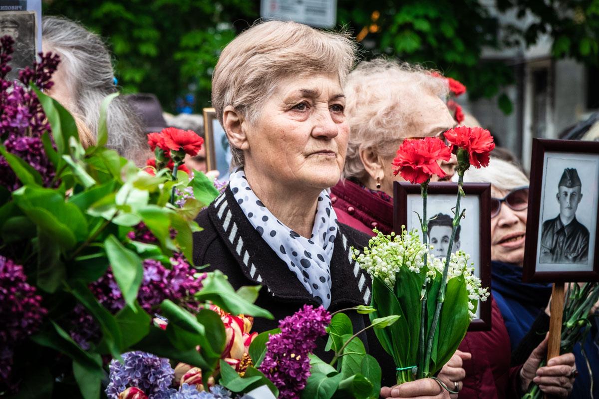 Люди прошли маршемпамяти к Парку Вечной Славы, держа в руках фотографию родственника - участника Второй мировой войны
