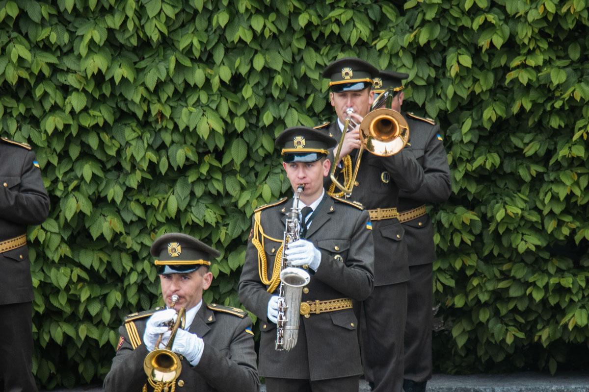 Военный оркестр играет у монумента