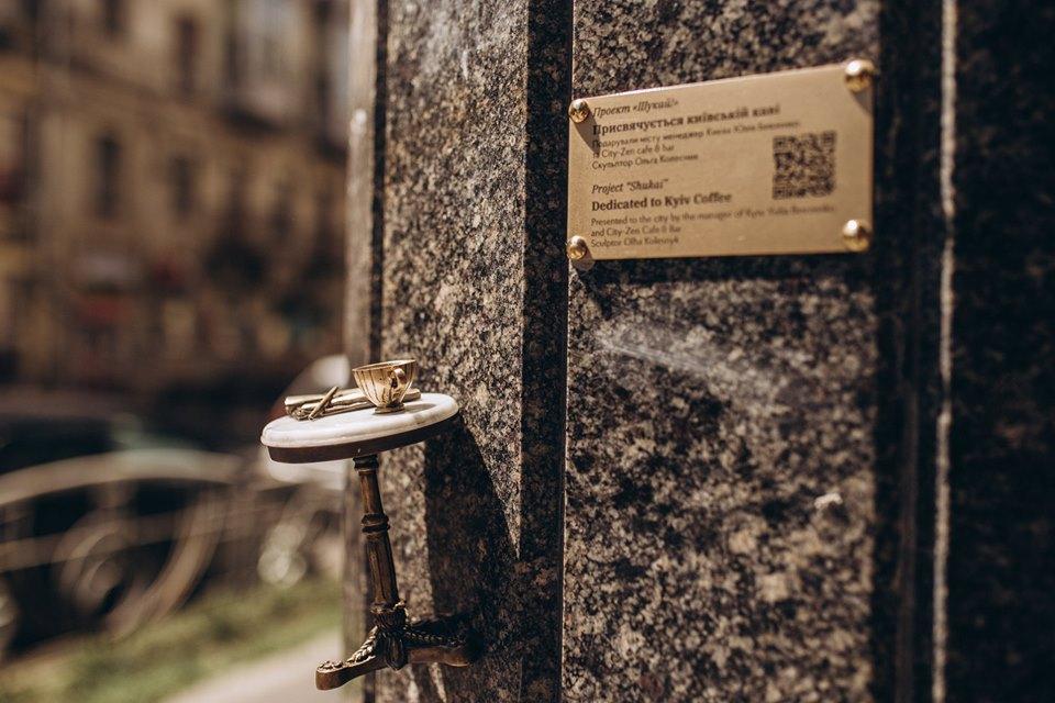 Столик, на котором стоит чашечка кофе и лежат карандаш с газетой, расположился на улице Большая Житомирская,20