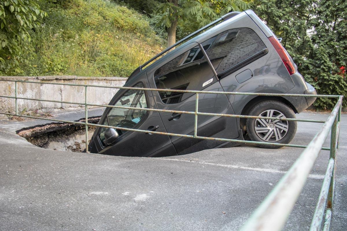 Машина оказалась наполовину в глубокой яме