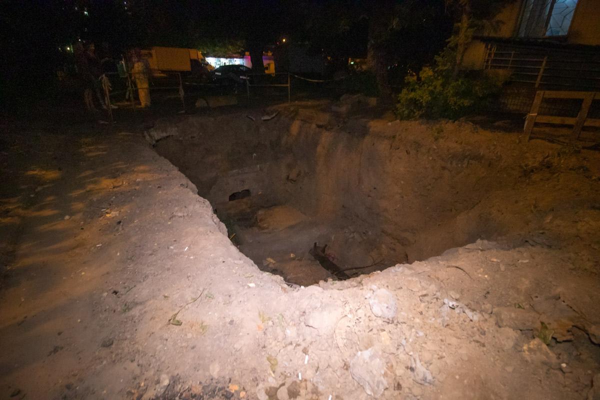 На улице Андрея Головко посреди двора находится яма, глубинок около 3-х метров