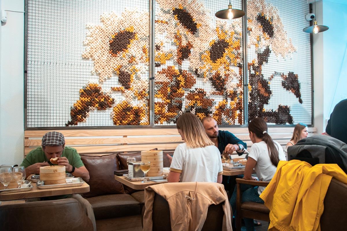 Стены в заведении украшает вышитая картина с подсолнухами