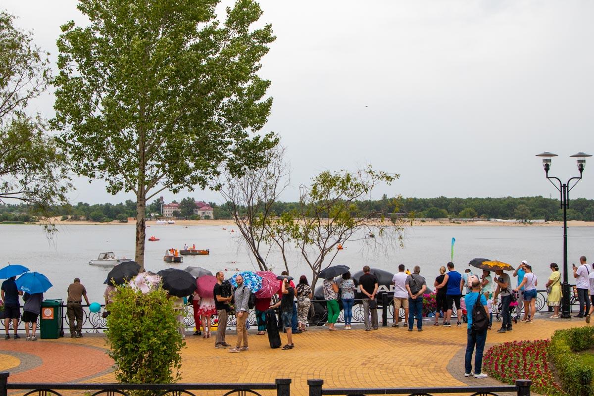В парке пошел дождь, поэтому люди спрятались под зонты и навесы