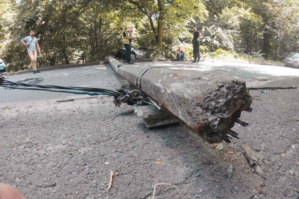 От удара столб упал и перегородил проезжую часть, а машины повисла на склоне