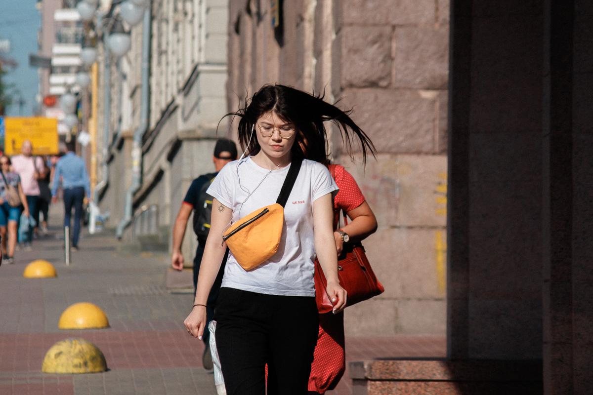 Она идет, а с ее волосами играет легкий ветер