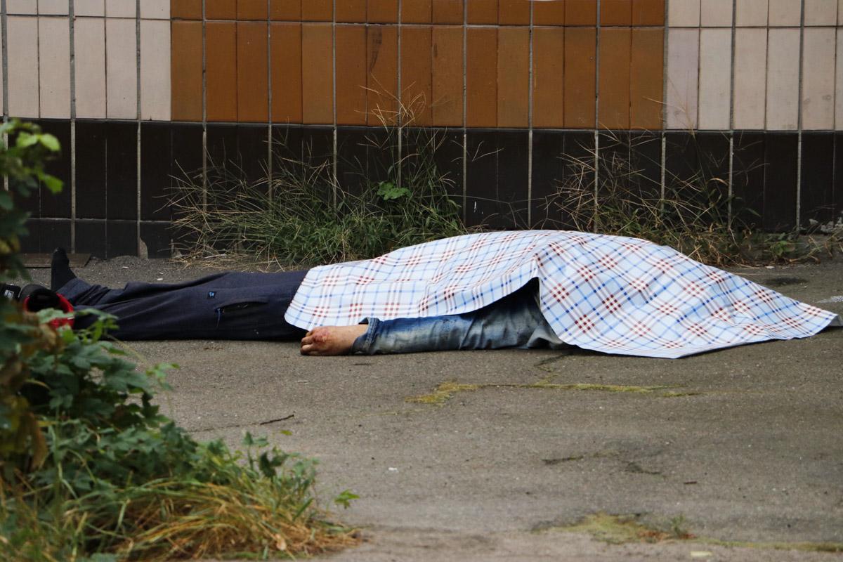 Тело с множественными ссадинами лежало под двухэтажным зданием