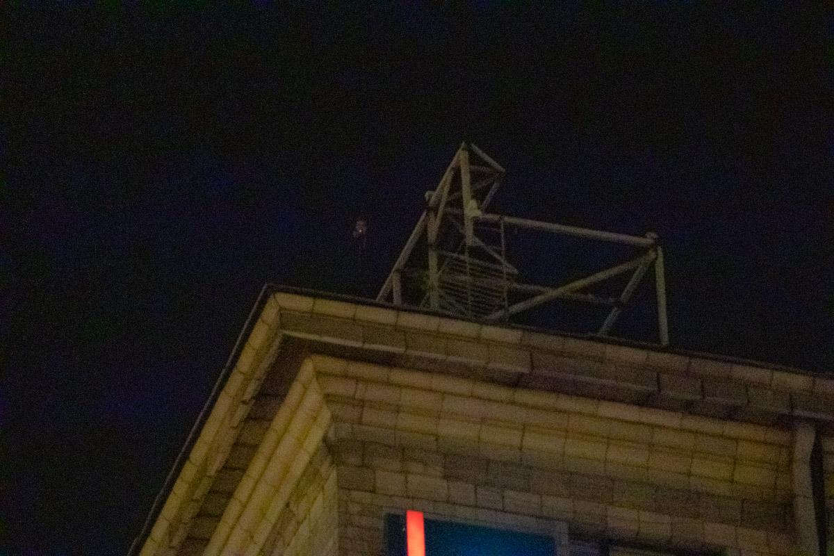 Евгений курит на углу крыши здания на Майдане