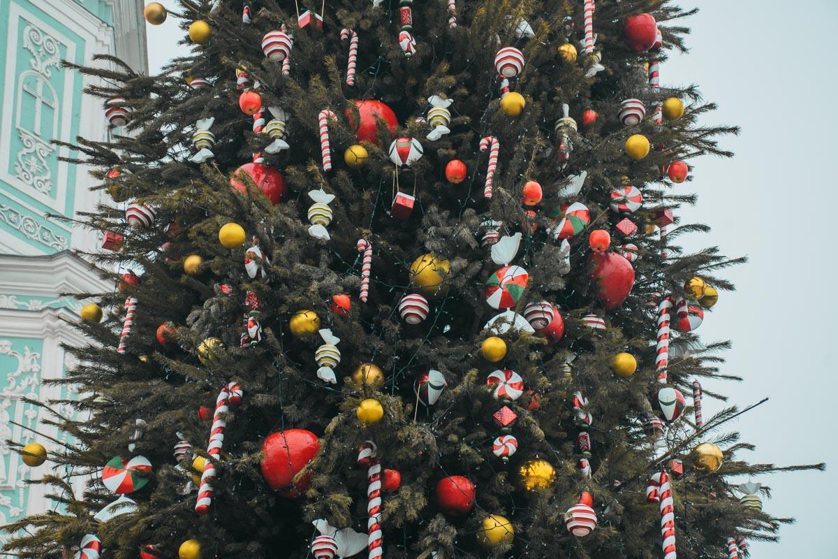 Елочку уже украсили игрушками в виде шаров, леденцов и яблок
