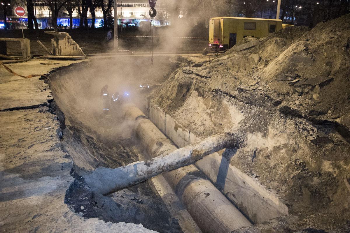 Сотрудники «Киевтеплоэнерго» полностью разрыли яму, где расположена теплотрасса, и разрезают трубу, чтобы достать ее по частям