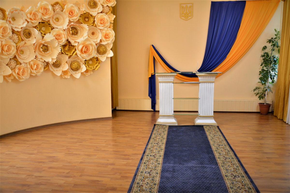 Святошинский зал для РАГС с большим флагом Украины и цветочной композицией на стене
