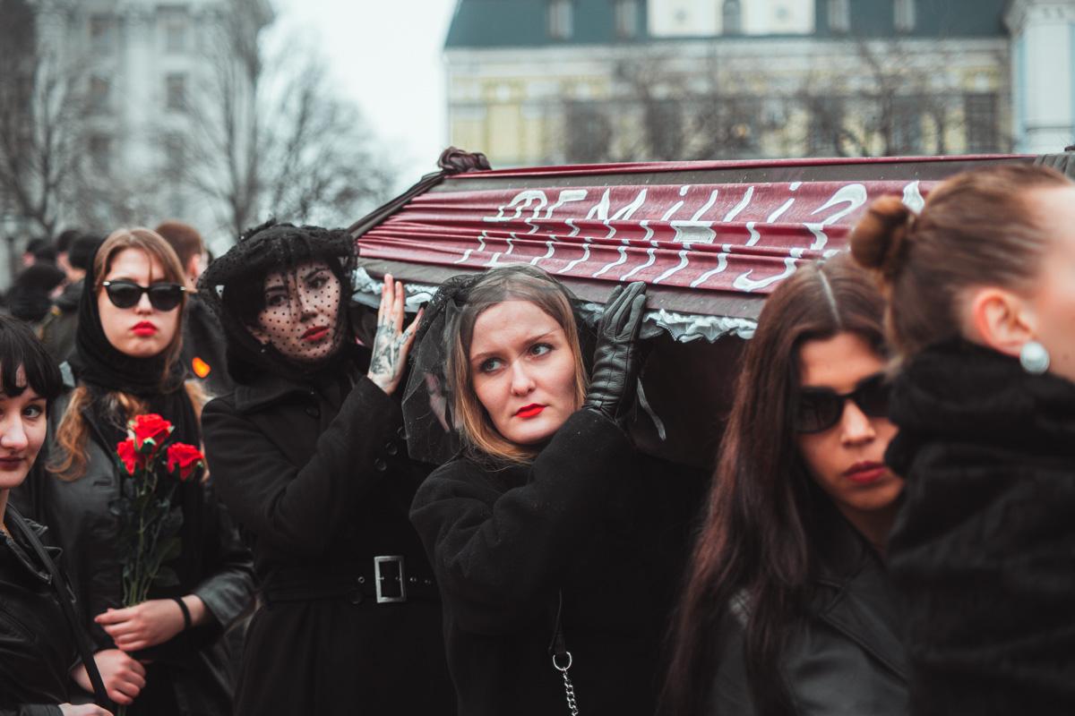 Чтобы привлечь внимание, девушки принесли на митинг гроб и венок, они устроили небольшой перформанс